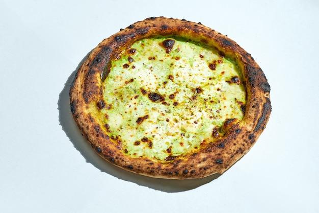 灰色の表面にモッツァレラチーズ、リコッタチーズ、パルメザンチーズ、ピスタチオを添えたおいしいイタリアの薪焼きピザ。ハードライト。