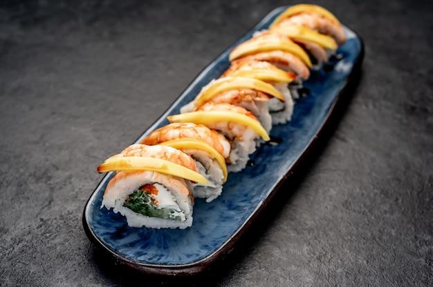 Вкусные японские суши-роллы на каменном фоне, готовые к употреблению