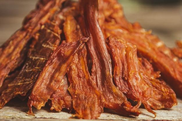Вкусное вяленое мясо на деревянном фоне. продукция в крафтовой упаковке. закуска к алкоголю. макро фото. крупный план.