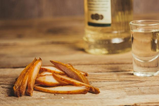 나무 배경에 맛있는 육포. 공예 포장 제품. 술을 위한 간식. 매크로 사진. 확대.
