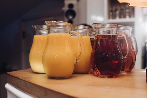 テーブルの上の瓶の中のおいしいジュース。木製のテーブルの上に新鮮なオレンジとベリージュースのいくつかの瓶。パーティーのコンセプト。