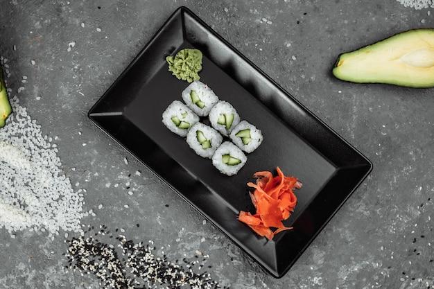 Вкусные, сочные и аппетитные маки с огурцом. суши на сером фоне.