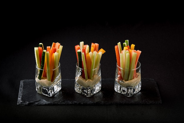 Delicious juicy cucumbers, carrots, celery, cut into thin strips or clubs, are served in a glass glass as snacks to plunge into a spicy sauce. fusion food concept, low key, copy space.