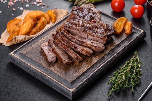 어두운 콘크리트 배경에 향신료와 허브를 곁들인 맛있는 육즙이 많은 신선한 쇠고기 스테이크. 구운 요리 프리미엄 사진