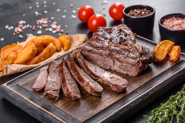 어두운 콘크리트 배경에 향신료와 허브를 곁들인 맛있는 육즙이 많은 신선한 쇠고기 스테이크. 구운 요리