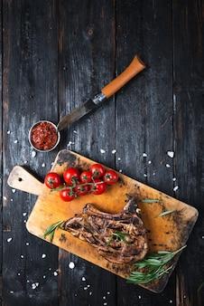 Вкусный сочный стейк на гриле, кусок мяса на столе, ароматные травы и специи, свежие овощи.