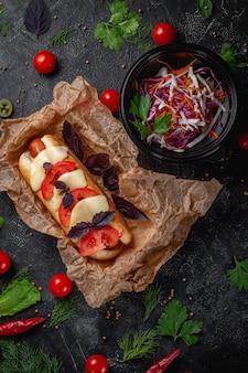 Вкусный сочный хот-дог с сырным соусом, помидорами и зеленью в ассортименте, бутерброд в меню ресторана быстрого питания на темном каменном столе. здоровый вариант быстрого питания.