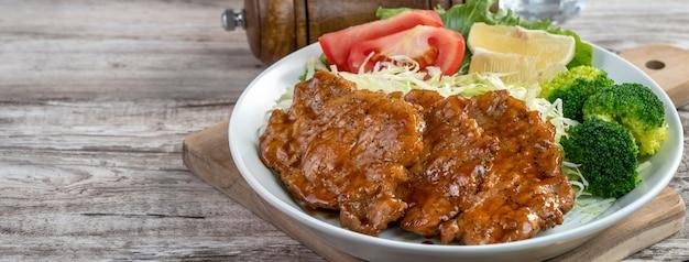 Вкусные сочные свиные отбивные с овощной едой в тарелке на обеденном столе.