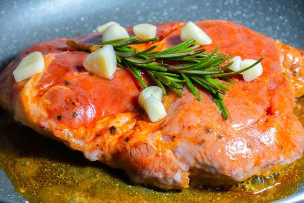 로즈마리와 마늘로 양념한 맛있는 육즙이 풍부한 돼지고기 스테이크를 팬에 튀겨냅니다.