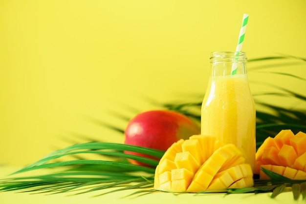 Delicious juicy smoothie with orange fruit and mango. fresh juice in glass bottles over green palm leaves.