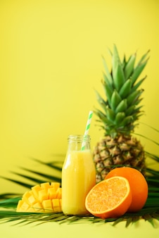 Delicious juicy smoothie with orange fruit, mango, pineapple. fresh juice in glass jar over green palm leaves.
