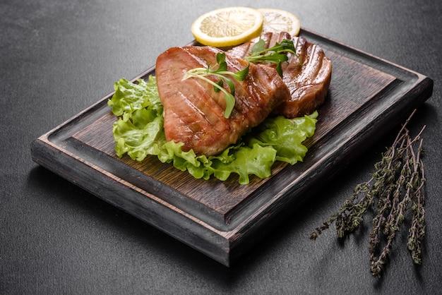 Вкусный сочный стейк из тунца на гриле со специями и зеленью и дольками лимона