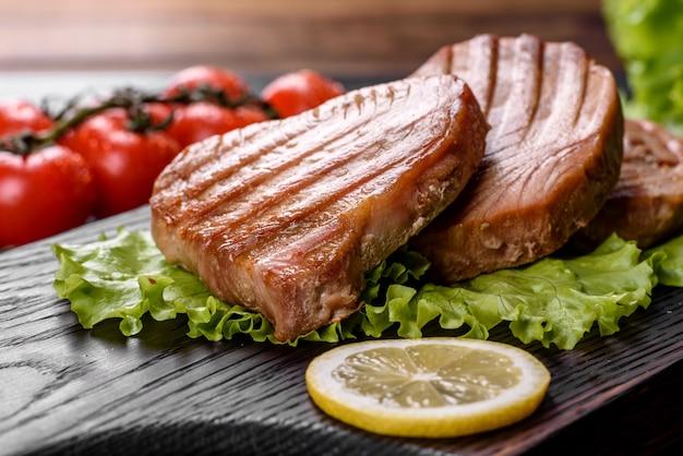 Вкусный сочный стейк из тунца на гриле со специями и зеленью