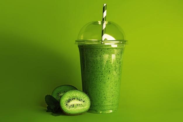 Вкусный молочный коктейль с киви в пластиковом стаканчике на зеленой поверхности