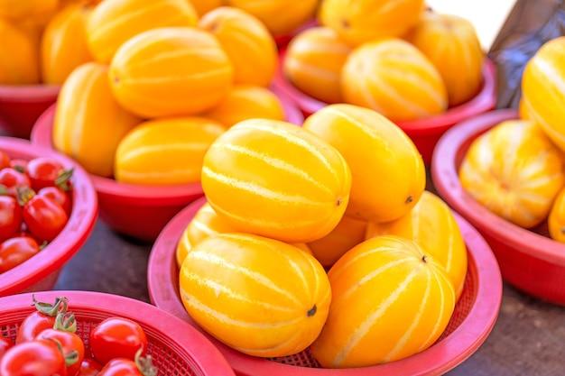 伝統的な市場で赤いプラスチックバスケットのおいしい韓国のストライプ黄色のメロンフルーツ食品