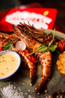 나무 테이블에 있는 레스토랑에서 맛있는 랑구스틴 새우 카페 메뉴에서 와인과 함께 맛있는 해산물
