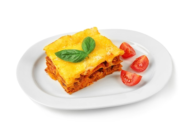 Delicious lasagna and tomatoes on white background