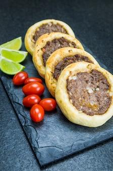 Вкусная ливанская еда, настоящие сфихи на грифельной тарелке с помидорами и лимонами.