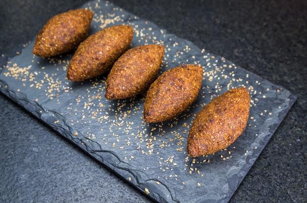 Вкусная ливанская еда, киббе (кибе) на черном сланцевом камне и гранитном фоне.