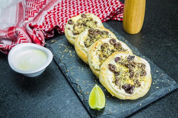 Вкусная ливанская кухня, средиземноморская рикотта сфиха, оливки в запеканке с сыром, на заднем плане - традиционная ливанская кефье.