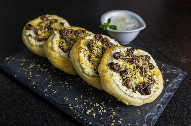 Вкусная ливанская еда, средиземноморская рикотта сфиха, оливки в запеканке с сыром на фоне черного гранита.