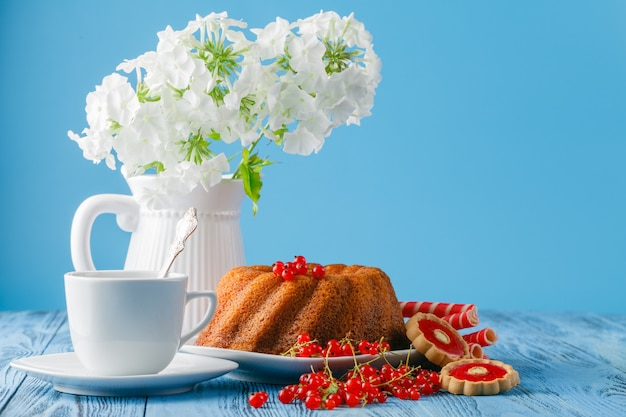 Delicious lemon cake on blue background with berries and flowers