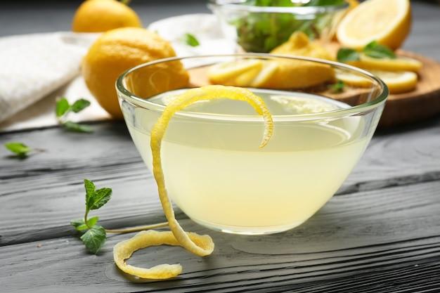 木製の背景のボウルにおいしいレモンジュース