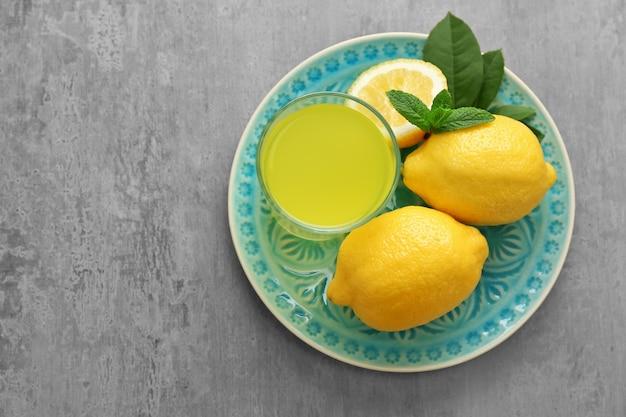 台所のテーブルの上のガラスのおいしいレモンジュース