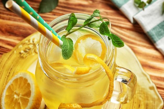 木製のテーブルの石工の瓶においしいレモンジュース