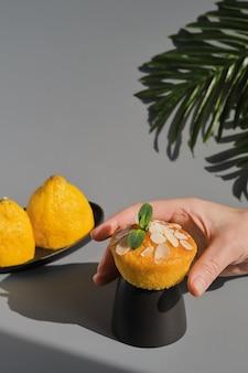 Delizioso muffin o cupcake al limone con glassa e scaglie di mandorle
