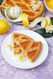 Delicious lemon pie slices with fresh lemons and a cup of tea on concrete, top view