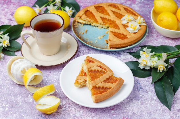Delicious lemon pie slices with fresh lemons and a cup of tea ,top view