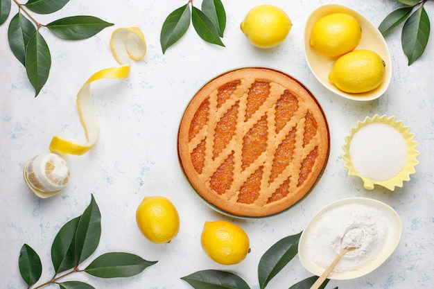Delicious lemon pie with fresh lemons on table