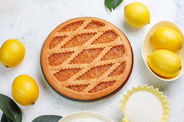 Delicious lemon pie with fresh lemons on table