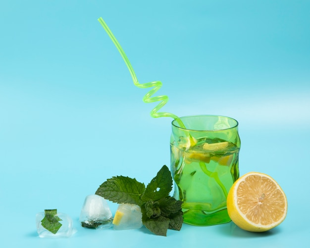 Delicious lemonade with mint leaves on blue background