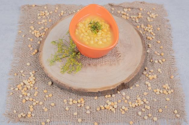 Delicious lentil soup with grain of lentil on wooden plate.