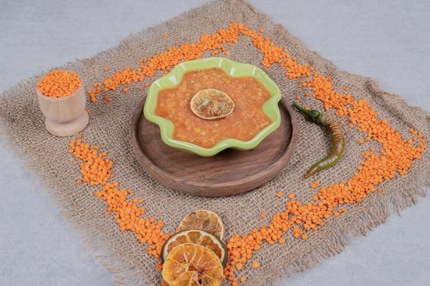 木の板にレンズ豆の粒が入ったおいしいレンズ豆のスープ。高品質の写真