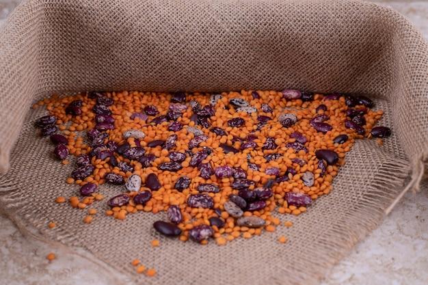 大理石の表面の木製のボウルにおいしいレンズ豆と豆。