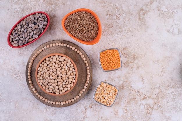 Lenticchie e fagioli deliziosi in piatti su fondo di marmo.