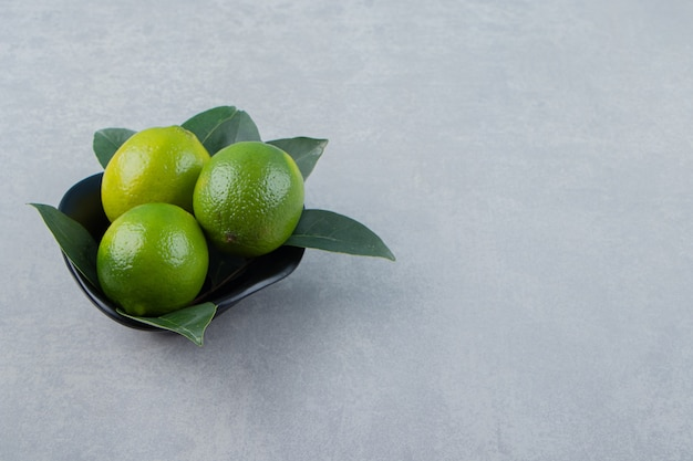 Delicious lime fruits in black bowl.