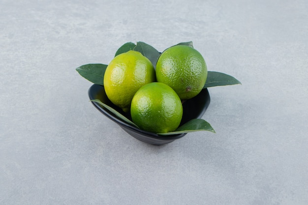 Delicious lime fruits in black bowl