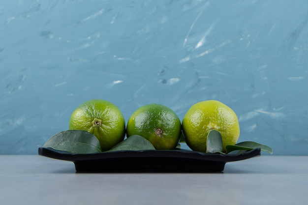 Delicious lime fruits on black plate.