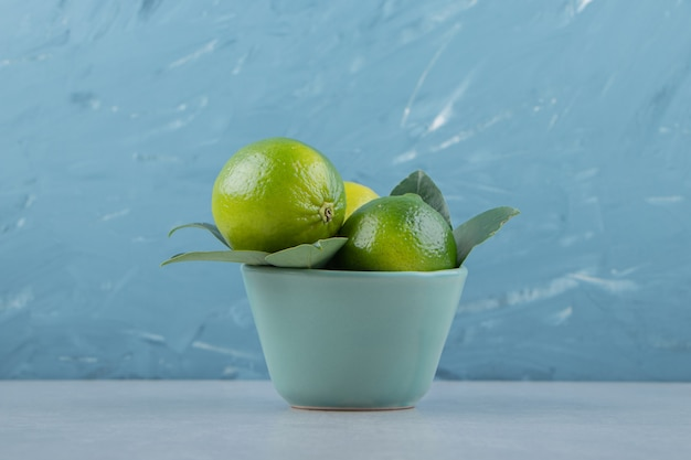 Delicious lime fruits in blue bowl.