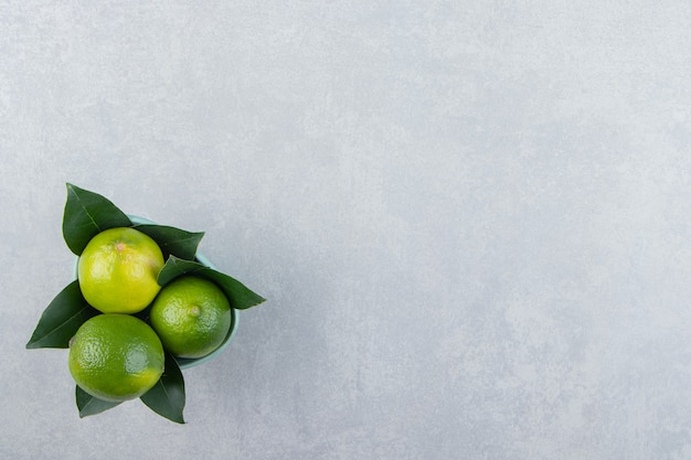 Delicious lime fruits in blue bowl
