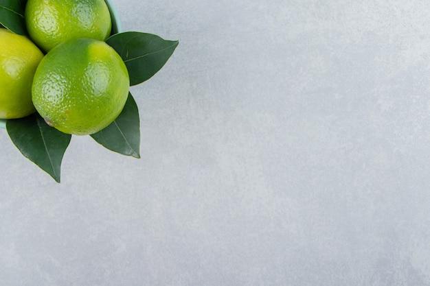 青いボウルにおいしいライムの果実。