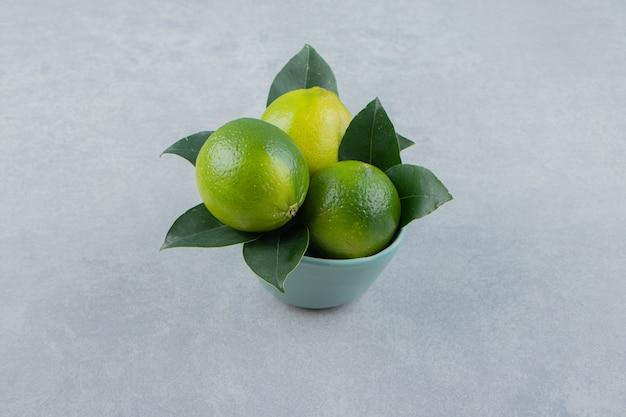 Вкусные плоды лайма в синей миске
