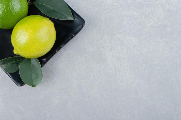 Вкусные фрукты лайма на черной тарелке