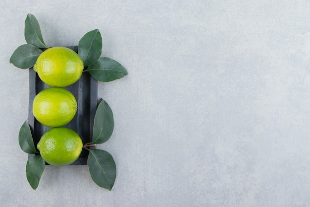 Delicious lime fruits with leaves on black plate