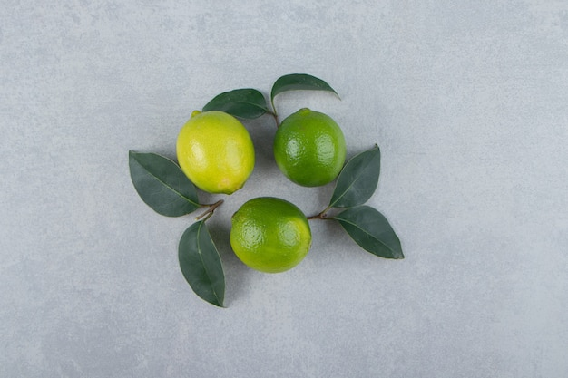 Delicious lime fruits with leaves on stone surface