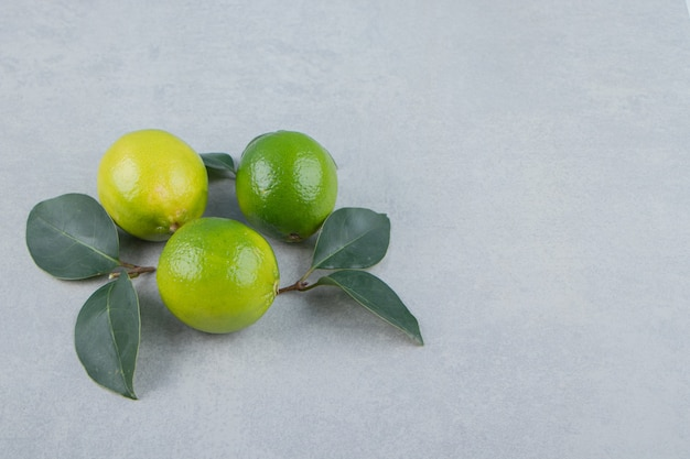 Delicious lime fruits with leaves on stone table.